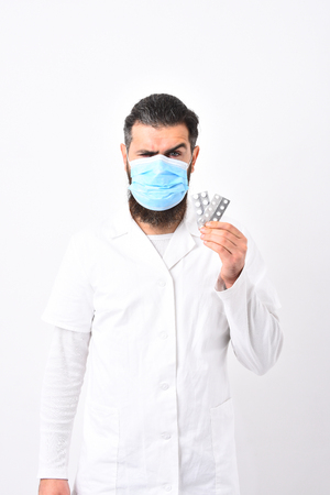 Medical worker with one eyebrow lifted. Medical worker holding pills up. Physician with beard dressed in white gown isolated on white background. Medicine and health concept.