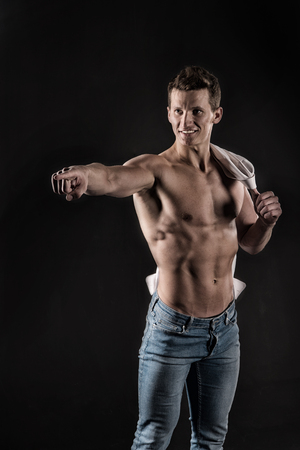 Man with muscular body. Athletic bodybuilder pose. Gladiator or atlant. Sport and workout. Guy with bare chest in jeans and shirt.