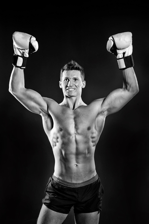 Gladiator or atlant in boxing gloves. Athletic bodybuilder pose in pants. Boxer with bare chest. Sport and workout. Man with muscular body, black and white