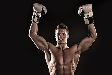 Man with muscular body. Boxer with bare chest. Sport and workout. Athletic bodybuilder pose in pants. Gladiator or atlant in boxing gloves. Stock Photo