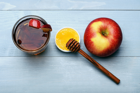 stirrer: set of glass with juice, pieces of apple, cinnamon, apple, honey, honey stick on grey-blue vintage wooden background, top view