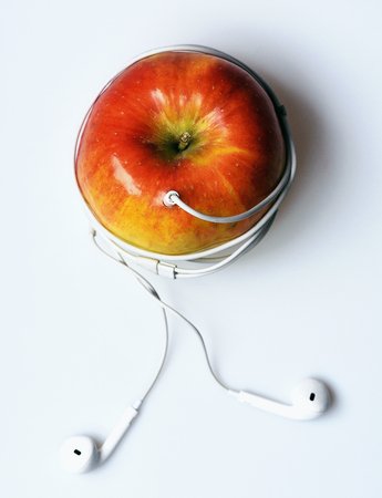 mp3 player: single orange or red color apple or fruit with vitamin for healthy diet and digital audio headphones for mp3 music player isolated on white background