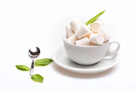 set of cup with marshmallow on plate with spoon and sheets of basil isolated on white background, side view, copy space
