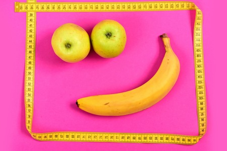 smiley pouce: Smiling face with green apples for eyes, ripe banana for mouth and yellow tape as square face, isolated on bright pink background. Happiness concept