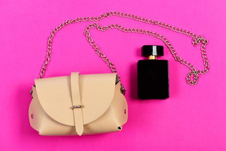 여성용 핸드백과 향수의 검은 병, 평면도. 마젠타 색 분홍색 배경에 현대적인 스타일의 액세서리입니다. 패션과 스타일 개념입니다. 밝은 베이지 색과