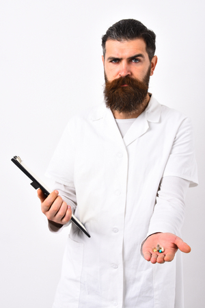 Medical doctor with stylish haircut holding black folder. Doctor with beard dressed in white gown isolated on white background. Physician with hesitating face gives pills. Medicine and health concept