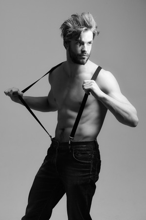 Handsome bearded man, fit macho with muscular torso poses in blue jeans and suspenders on grey background Stock Photo