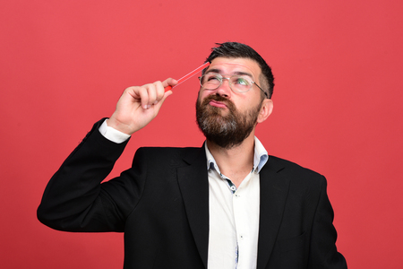 Success, business and brainstorming concept. Man in classic outfit with beard holds red marker. Businessman with thoughtful face and glasses on light red background. Guy generates ideas