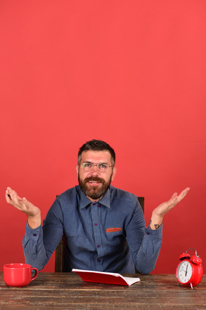 barbershop: Teacher with beard and glasses sits near notebook, red background. Man with puzzled smiling face sits at wooden table. Cup, retro clock and red book on vintage table. Exam and studying concept