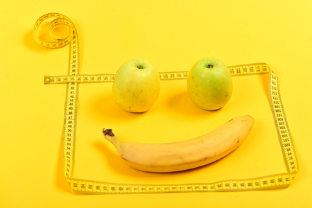 Emoticon made of ripe apples and banana with tape for measuring, isolated on bright yellow background. Concept of vitamins and eco food