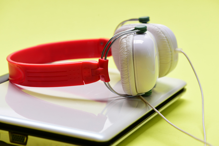Sound recording idea. Earphones in red and white colors made of plastic with computer. Electronics on light yellow background. Headphones and silver laptop. Music and digital equipment concept Stock Photo