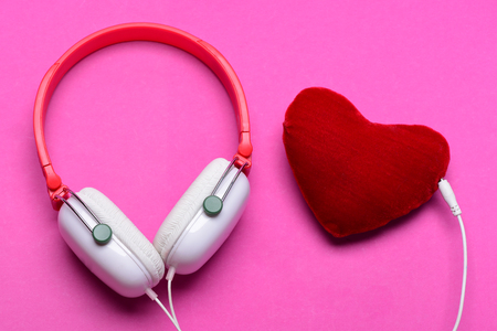shaped: Modern and stylish earphones isolated on pink background. Music accessories and Valentines day concept. Headset for music and heart shaped player. Headphones in white and red color with soft toy heart Stock Photo