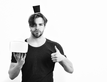 barbershop: Bearded man, short beard. Caucasian sexy young macho with stylish hair and moustache on serious face holding male box with coffee cup on head in blue shirt isolated on white studio background