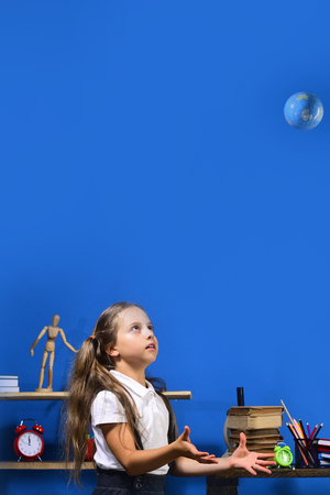 Girl in classroom with colorful stationery and books. Schoolgirl with scared face throws globe model up. Kid and school supplies on blue background, copy space. Back to school and geography concept
