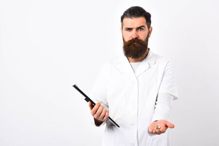 Medical worker with stylish haircut holds black folder in hand. Medicine and health concept. Doctor with beard dressed in white lab coat isolated on white. Physician with hesitating face offers pills