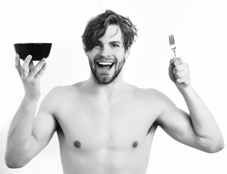 barbershop: Bearded man, short beard. Caucasian sexy young macho with stylish hair, moustache on smiling happy face shows muscular torso holding black bowl with fork isolated on white studio background Stock Photo