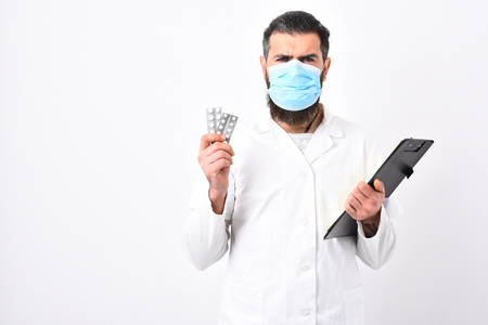 Physician with beard dressed in white gown. Medicine and health concept. Medical doctor with stylish haircut holds black folder and pills. Doctor with angry face in medical mask isolated on white
