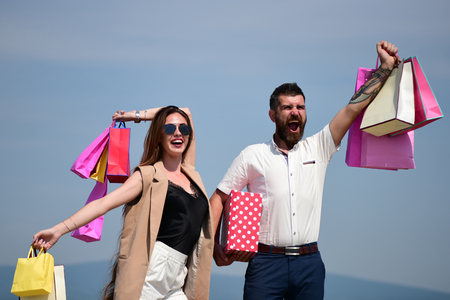 barbershop: Man with beard and long haired woman hold shopping bags. Shopping and shopaholism concept. Couple carries pink packets and box on blue sky background. Sexy girl and guy with happy faces make purchases