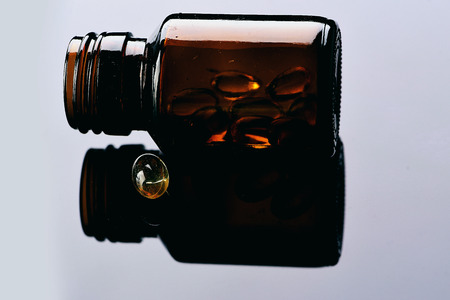 Pills pouring out of the brown glass bottle on light grey background with reflection, close up. Health concept Stock Photo