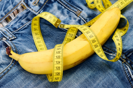 Health and male concept. Banana wrapped with yellow measure tape on jeans, selective focus. Jeans zipper and pocket, close up.