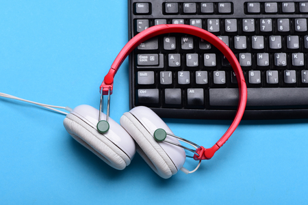 Electronic appliances on turquoise background. Headphones and black keyboard. Music and digital equipment concept. Sound recording idea. Earphones in red and white colors with computer keyboard