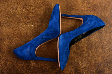 expensive: High heel shoes in dark blue. Pair of fancy suede female shoes, top view. Formal female footwear. Fashion and beauty concept. Womens shoes on old brown suede background