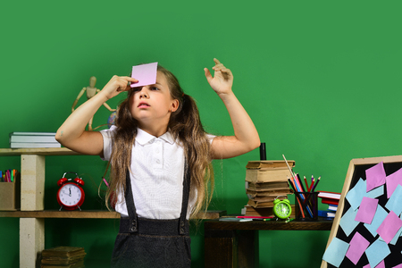 Kid and school supplies on green wall background. Back to school and childhood concept. Schoolgirl with concentrated face in her classroom. Girl sticks pink note to her forehead standing by blackboard