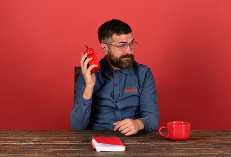 Cup, retro clock and red book on vintage desk. Deadline and work concept. Worker with beard and glasses holds and listens to alarm clock, red background. Man with unsatisfied face sits at wooden table