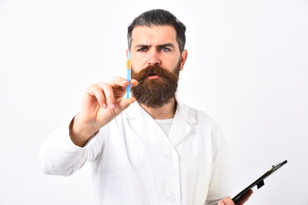 medical doctors: Doctor with concentrated face isolated on white background. Bearded doctor with stylish haircut holds syringe and black folder. Physician looking on needle with one eye. Medicine and health concept