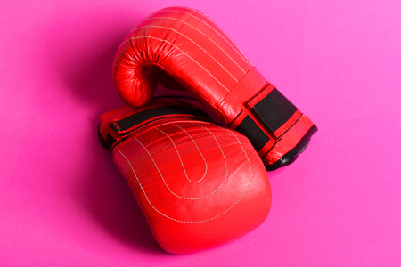 Pair of gloves for boxing in bright red color, isolated on pink background. Concept of sports and fighting