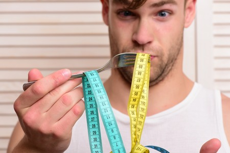 Tape for measuring in yellow and cyan colors on fork. Diet and health concept. Man with surprised face expression beige jalousie background. Guy in sleeveless shirt looks at flexible ruler Stock Photo