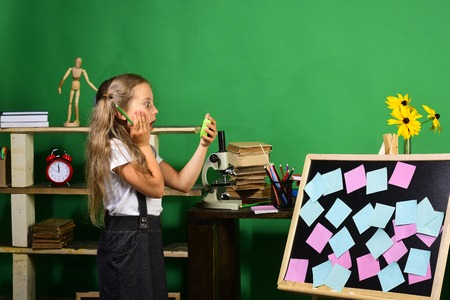 Girl holds green clock and pencil standing by blackboard with colored notes. Back to school and deadline concept. Schoolgirl with shocked or worried face. Kid and school supplies on green background Stock Photo