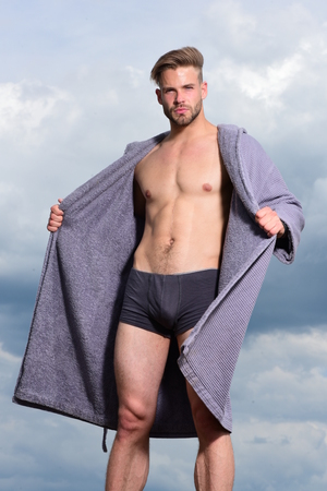 Male model posing against the sky. Morning concept. Sexy young macho on the sky. Bearded attractive guy enjoy healthy morning. Adult handsome man in fashionable bathrobe. Stock Photo