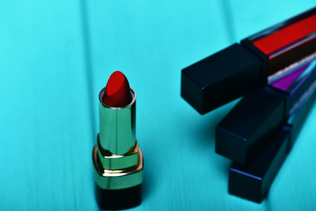 red lipstick and various lip glosses on turquoise blue wooden background, side view, selective focus Stock Photo