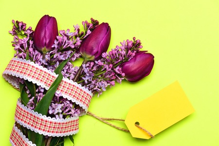 Tulips and lilac flowers in bunch with striking yellow price label isolated on light yellow background, top view and copy space. Concept of taking notes and spring time Stock Photo