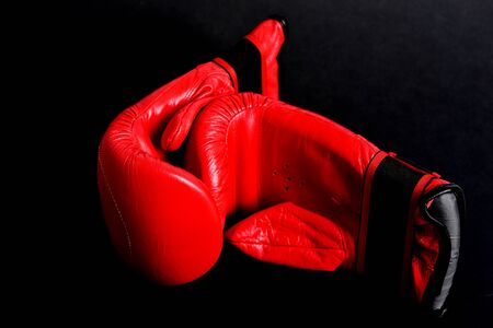 Couple of red mittens for boxing lain next to each other isolated on black background. Idea of sports equipment and knock down Stock Photo