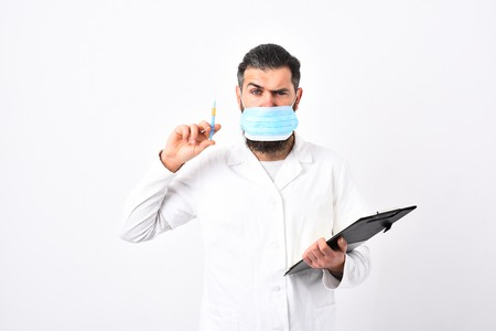Medical doctor with stylish haircut holds black folder and syringe. Physician wears medical face mask isolated on white background. Doctor with beard dressed in white gown. Medicine and health concept