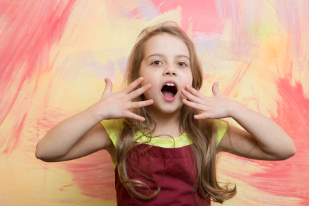 Girl cook with open mouth on surprised face posing in red chef apron on colorful abstract wall. Child and childhood. Cooking concept 스톡 콘텐츠