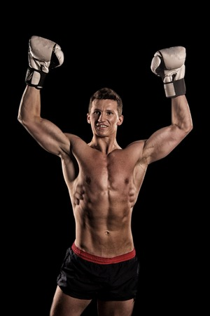 Gladiator or atlant in boxing gloves. Boxer with bare chest. Athletic bodybuilder pose in pants. Sport and workout. Man with muscular body. Stock Photo
