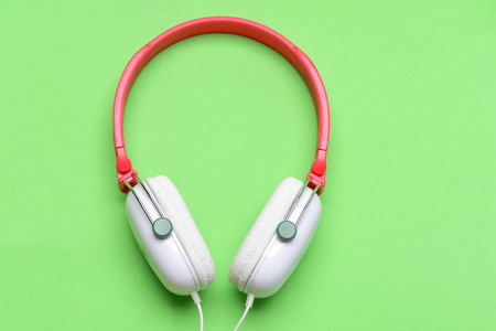 Headphones in white and red color with long wire. Music accessories and technology concept. Headset for music made of plastic. Modern and stylish earphones isolated on light green background, top view
