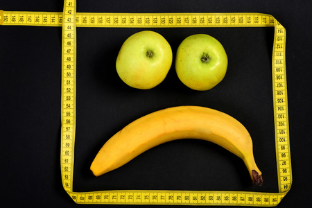 smiley pouce: Fruit and face. Sad smiley expression made of fruit and frame of measuring tape on black background, close up. Concept of emotions and minimalism