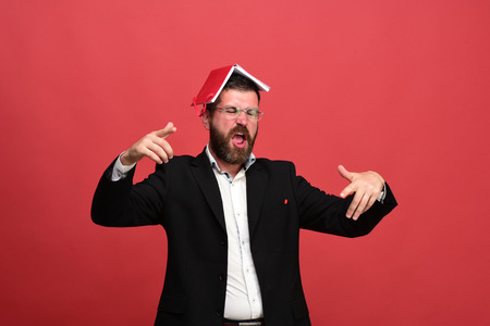 Businessman with hooligan face and glasses on light red background. Man in classic outfit with beard holds red book on head. Success and business concept. Guy with open notebook and pen in jacket