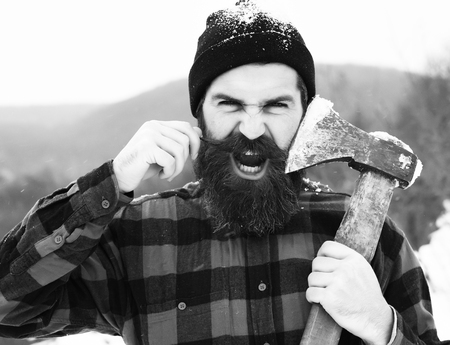 Angry man or brutal lumberjack, bearded hipster, with beard and moustache in red checkered shirt shaves with axe blade in snowy forest on winter day outdoors on natural background Banco de Imagens