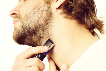 Mans neck with fair beard. Bearded guy and shaver isolated on white background, close up. Barbershop and morning routine concept. Man holds razor and starts shaving his beard Stock Photo