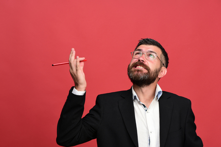 Man in classic outfit with beard holds red marker. Businessman with thinking face and glasses on light red background. Guy with pen in hand generates ideas. Success, business and brainstorming concept