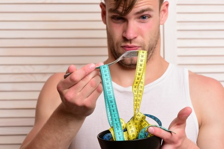 Guy in sleeveless shirt eating measuring tape. Athlete with unshaved face. Diet and health concept. Man with surprised face expression on background of beige jalousie.