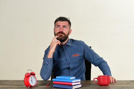 Man with thinking face sits at wooden desk. Cup and retro clock with red and blue books on vintage table. Worker with beard and glasses on head isolated on white background. Deadline and work concept