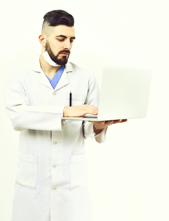 Man with busy face expression in white coat. Doctor with beard types on white laptop. Physician wears surgical mask isolated on white background. Treatment and medical technologies concept