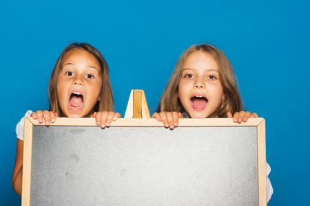 Children with opened mouths, copy space. Girls in school uniform on blue background. Education and school concept. Schoolgirls with surprised faces stand near blackboard.