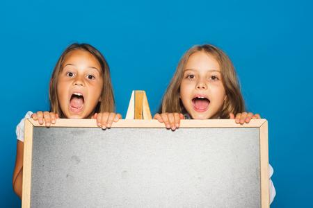 Kinderen met geopende mond, kopie ruimte. Meisjes in schooluniform op blauwe achtergrond. Onderwijs en school concept. Schoolmeisjes met verraste gezichten staan in de buurt van schoolbord.